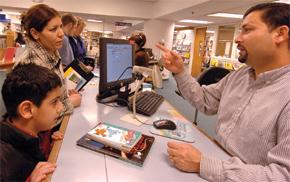 Na snímku asistent Mani Neupane pomáhá paní Shahle Mostafavi a jejímu synovi s výběrem knih v Gaithersburgské knihovně v Marylandu. Foto Getty Images