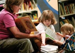 Elizabeth Darrah  z městečka Anderson v Jižní Karolíně sleduje dceru Rebeku, jak sahá po knize, zatímco její nejmladší dcera Sarah Beth si prohlíží knihu v Dětské knihovně Scrippse Howarda v Andersonu. Rodina navštívila program, který má děti mladší šesti let přilákat k četbě.  Foto AP Images